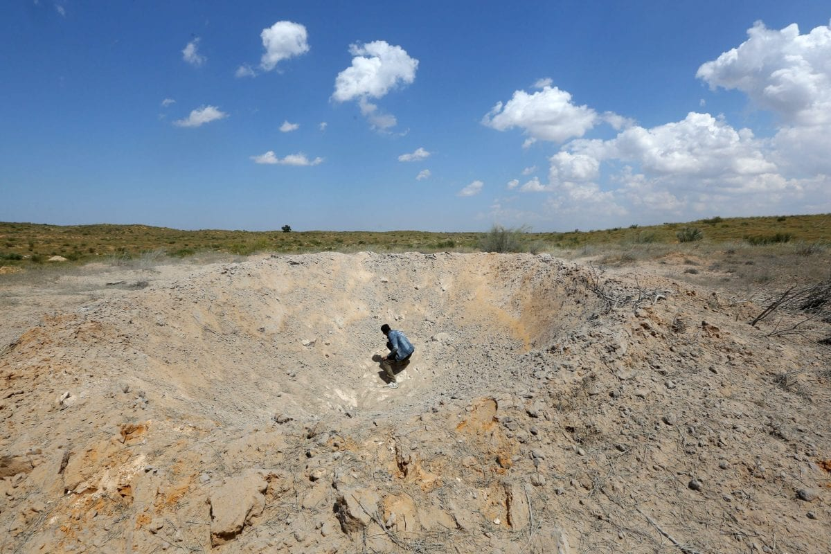 A fighter loyal to Libya's Government of National Accord (GNA) sits in a crater reportedly caused by an air strike west of the city of Aziziah, some 60 kilometres southwest of the capital Tripoli, on 14 April 2019. [Mahmud TURKIA / AFP / Getty]