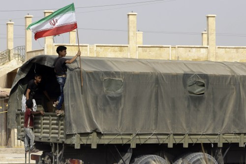 A Syrian boy holds the Iranian flag as a truck carrying aid provided by Iran arrives in Syria on 20 September 2017 [AFP PHOTO/LOUAI BESHARA/Getty]