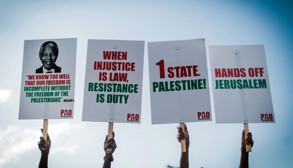 People hold placards during a demonstration by pro-Palestinian groups and other civil society organisations, in Durban on 2 June 2018 to protest against the killing of Palestinians by Israeli forces in Gaza. [RAJESH JANTILAL/AFP/Getty Images]