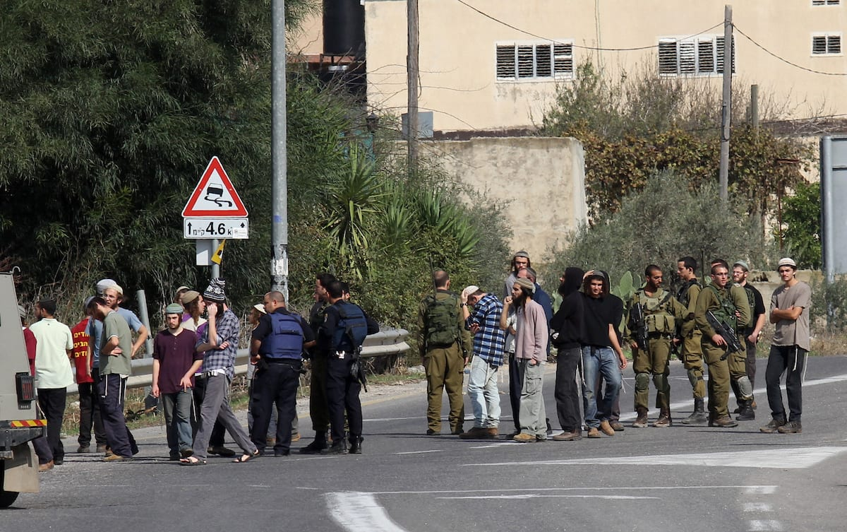 Israeli police officers and Jewish settlers close the main street, leading to the settlement of Yitzhar near the West Bank city of Nablus, on 8 Nov. 2015. [Nedal Eshtayah/Apaimages]