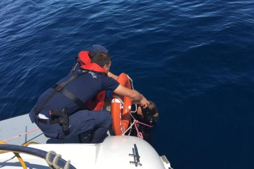 Turkish Coast Guard members rescue a woman after a boat carrying irregular migrants sank off in Ayvalik district of Balikesir, Turkey on May 3, 2019. At least 7 irregular migrants drowned and 5 of them are reported missing off after the boat sank off the coast of Ayvalik district of Balikesir [Turkish Coast Guard Command/Handout/Anadolu Agency]