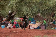 Syrian families, with their belongings are seen as they take shelter near Turkey's border in Idlib, Syria on 6 May, 2019 [Muhammed Abdullah/Anadolu Agency]