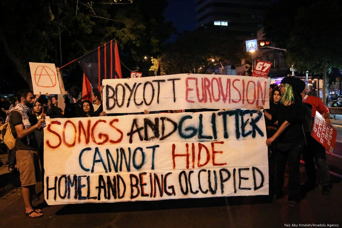 People hold placards during a protest against the Eurovision Contest demanding the removal of Israel's blockade on Gaza in Tel Aviv on 14 May 2019 [Faiz Abu Rmeleh/Anadolu Agency]