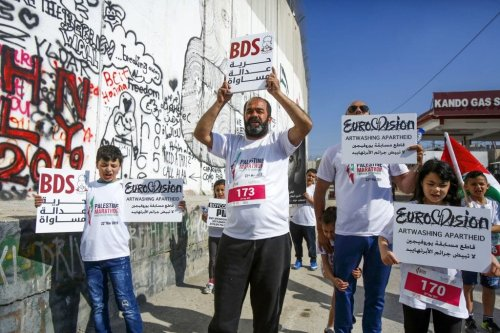 Activists hold placards calling for the boycott of Eurovision along Israel's controversial separation barrier, which divides the West Bank from Jerusalem, during the 7th International Palestine Marathon in the biblical town of Bethlehem in the occupied West Bank on 22 March 2019. [MUSA AL SHAER/AFP/Getty Images]