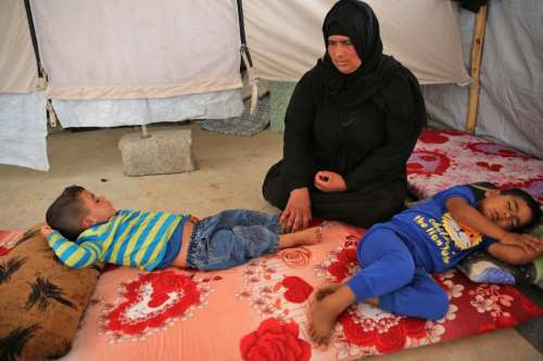 Salima, a 36-year-old mother of four living in the Laylan 2 displacement camp, sits with her children in their tent at the camp, southeast of Kirkuk in northern Iraq on May 9, 2019. [AHMAD AL-RUBAYE / AFP/ Getty]