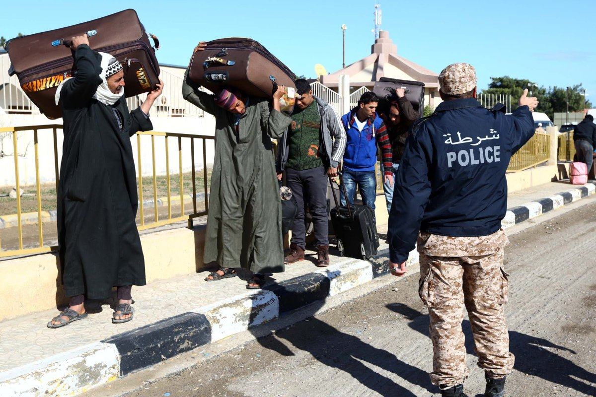 Egyptians walk carrying their belongings in Libya on 23 February 2015 [MAHMUD TURKIA/AFP/Getty Images]