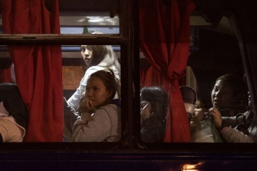 Filipina workers returning home from Kuwait inside a bus after arriving at Manila International Airport on 17 February 2018. [NOEL CELIS/AFP/Getty Images]