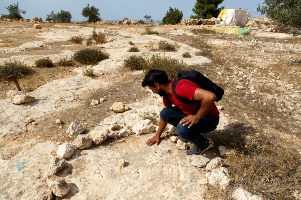 Ibrahim Nawaja, 30, uncovers a rock which has the date of the 1997 Susiya demolitions inscribed into it