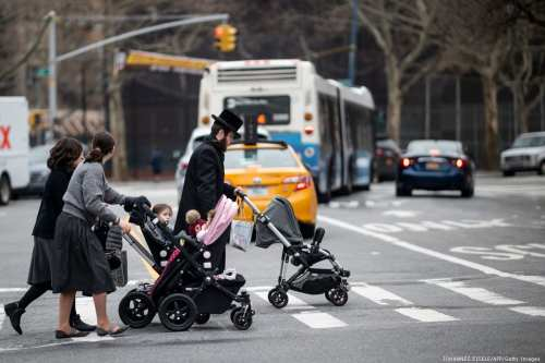 A Jewish man and two woman push strollers as they cross a street in New York City, US on 9 April 2019 [JOHANNES EISELE/AFP/Getty Images]