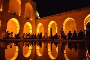 People sit by a pond at historical Kasimiye Madrasa as people gathered for a Tarawih prayer during Muslims' holy fasting month of Ramadan in Artuklu district of Turkey's southeastern Mardin province on 1 June, 2019 [Halil İbrahim Sincar/Anadolu Agency]