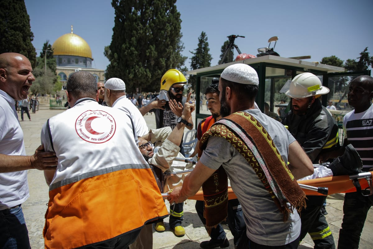 injured Muslim is being carried away with Palestinian health care members, after Israeli police officers intervene them with tear gas canisters, as fanatic Jews, under Israeli police protection, raid Al-Aqsa Mosque Compound in Jerusalem on 2 June 2019. [Faiz Abu Rmeleh - Anadolu Agency]