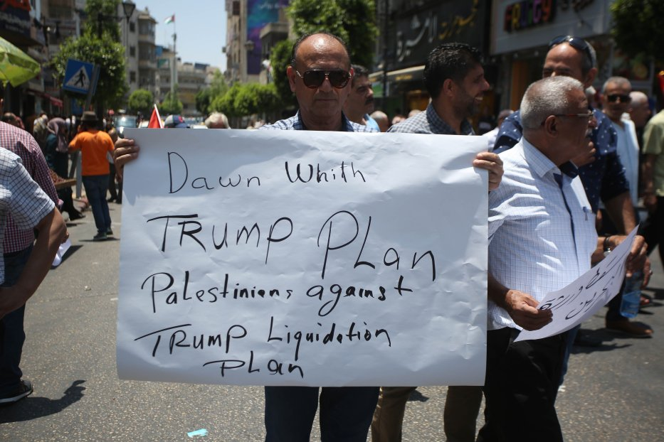 "Palestinians hold banners as they gather to protest against a conference, which is the workshop, scheduled for June 25 and 26, in Bahrain's capital Manama, related with a ""Deal of the Century"" plan in Ramallah, West Bank on 15 June 2019. [Issam Rimawi - Anadolu Agency]"