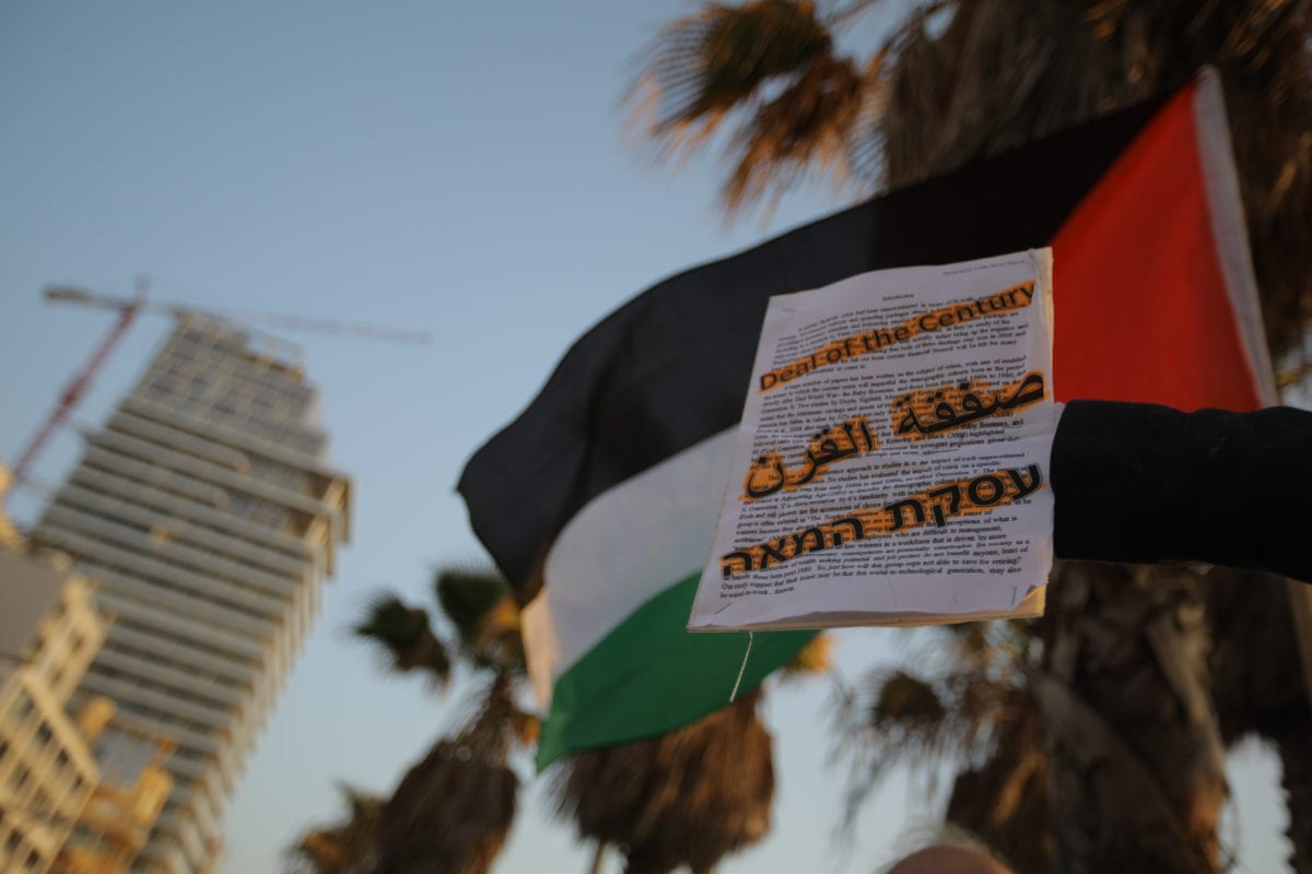Palestinians hold placards and Palestinian flag as they gather to protest against 'Deal of the Century' plan in Tel Aviv on 25 June 2019 [Faiz Abu Rmeleh/Anadolu Agency]