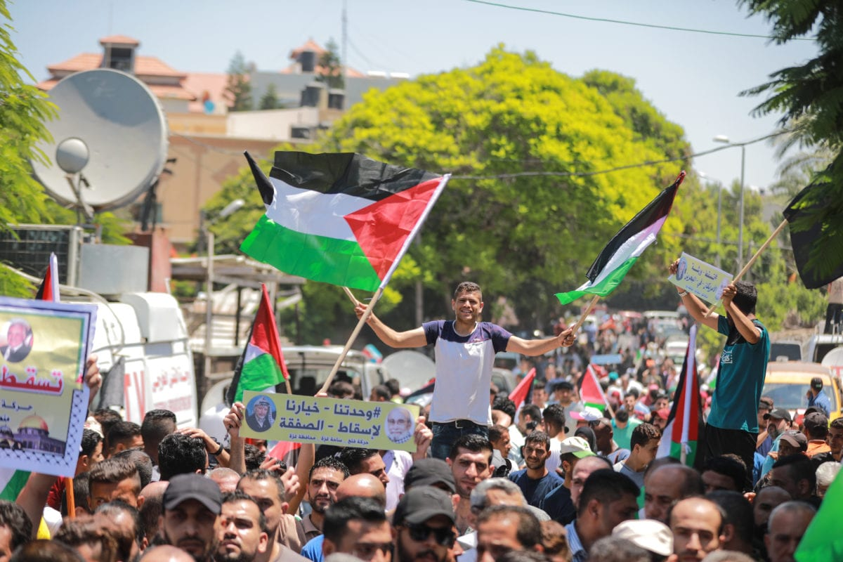 People gather to stage a demonstration against the US-led conference in Bahrain, on June 26, 2019 in Gaza City, Gaza. [Ali Jadallah - Anadolu Agency]