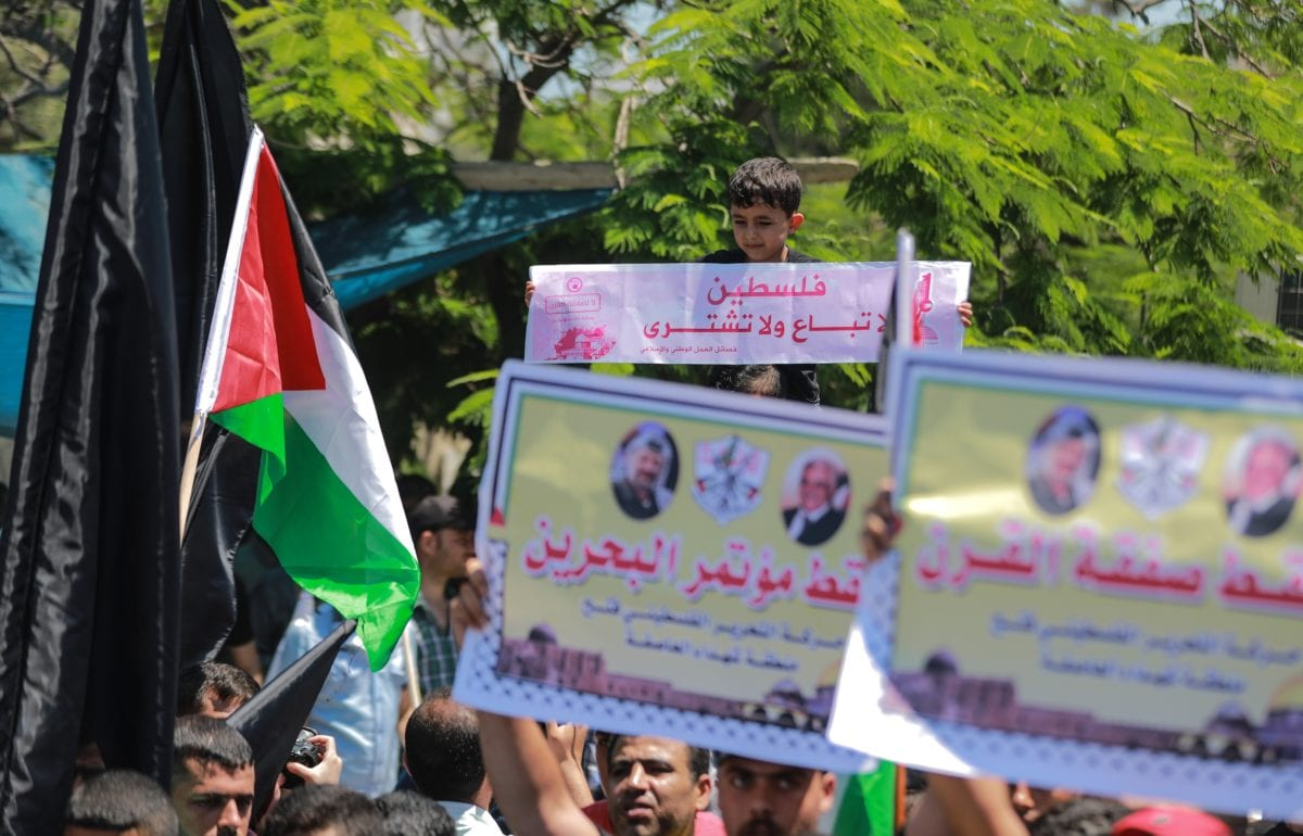 People hold banners during a demonstration against the US-led conference in Bahrain, on 26 June 2019 in Gaza City, Gaza. [Ali Jadallah - Anadolu Agency]