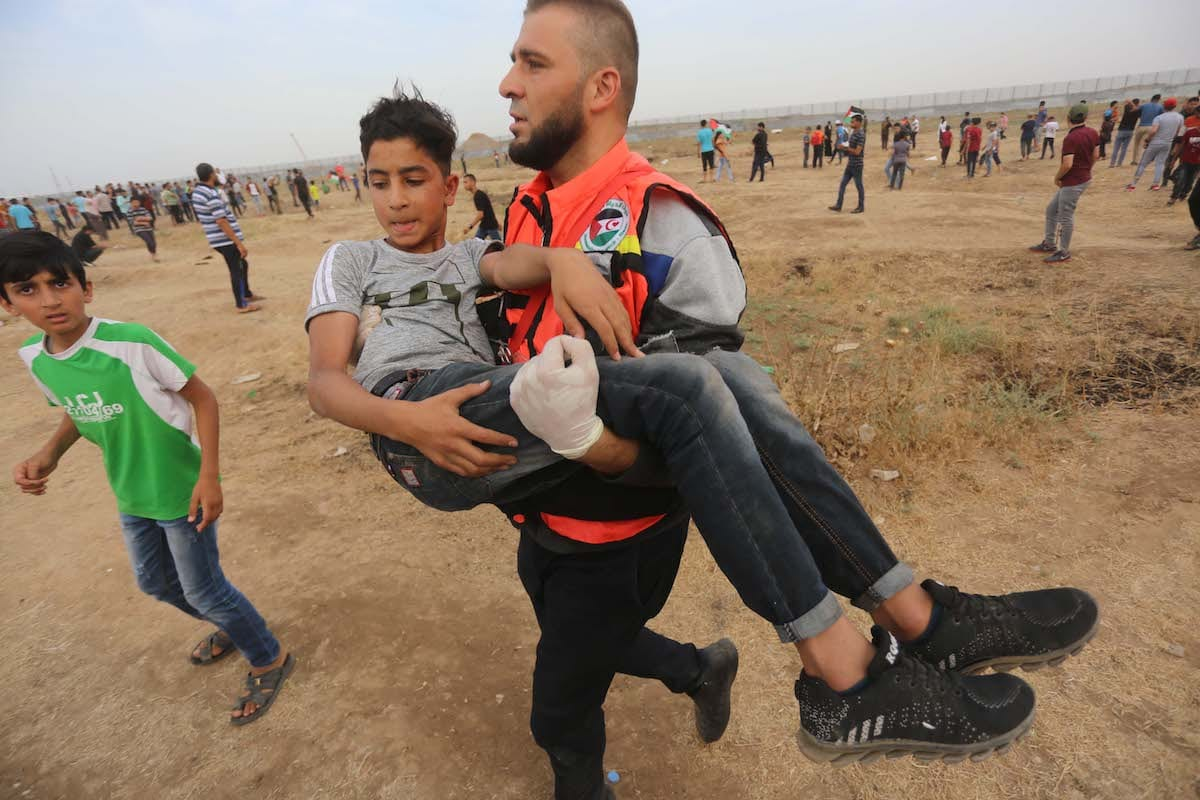 Medics carry an injured Palestinian after Israeli forces fired at protesters during the Great March of Return in Gaza on 31 May 2019 [Mohammed Asad/Middle East Monitor]