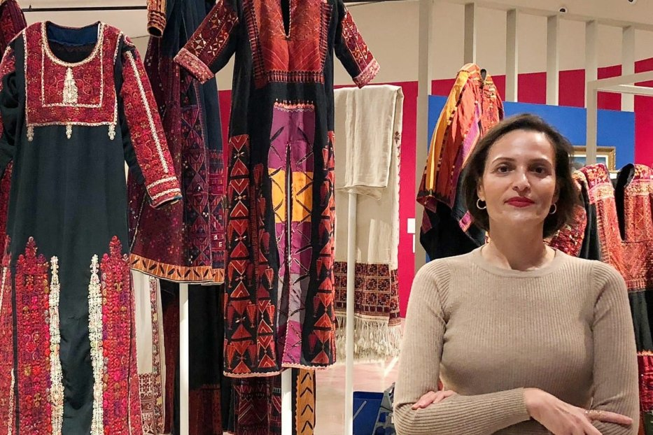 Dr Adila Laïdi Hanieh stands in-front of the Palestine Museum 2018 exhibition: labour of love. New approaches to Palestinian embroidery [Lena Sobeh]