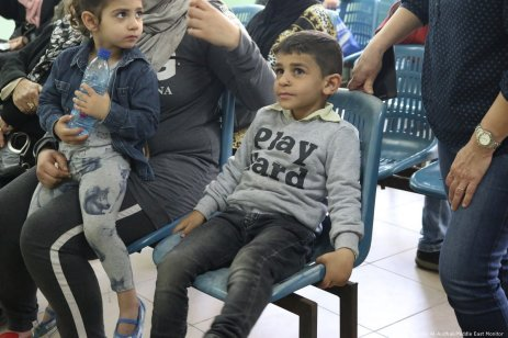 Young children sat with their mother in the waiting room of an UNRWA clinic [Ferdous Al-Audhali/Middle East Monitor]