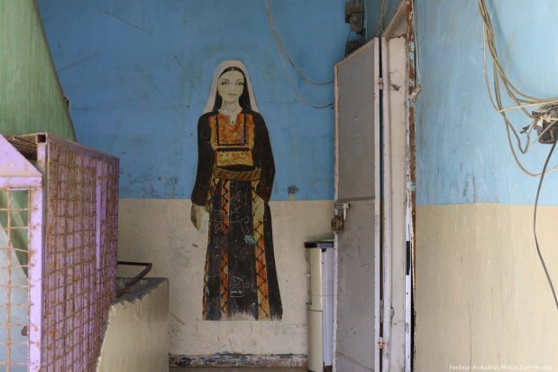 A drawing of a woman wearing traditional Palestinian dress painted on a wall outside Nada, an NGO which encourages traditional Palestinian embroidery.