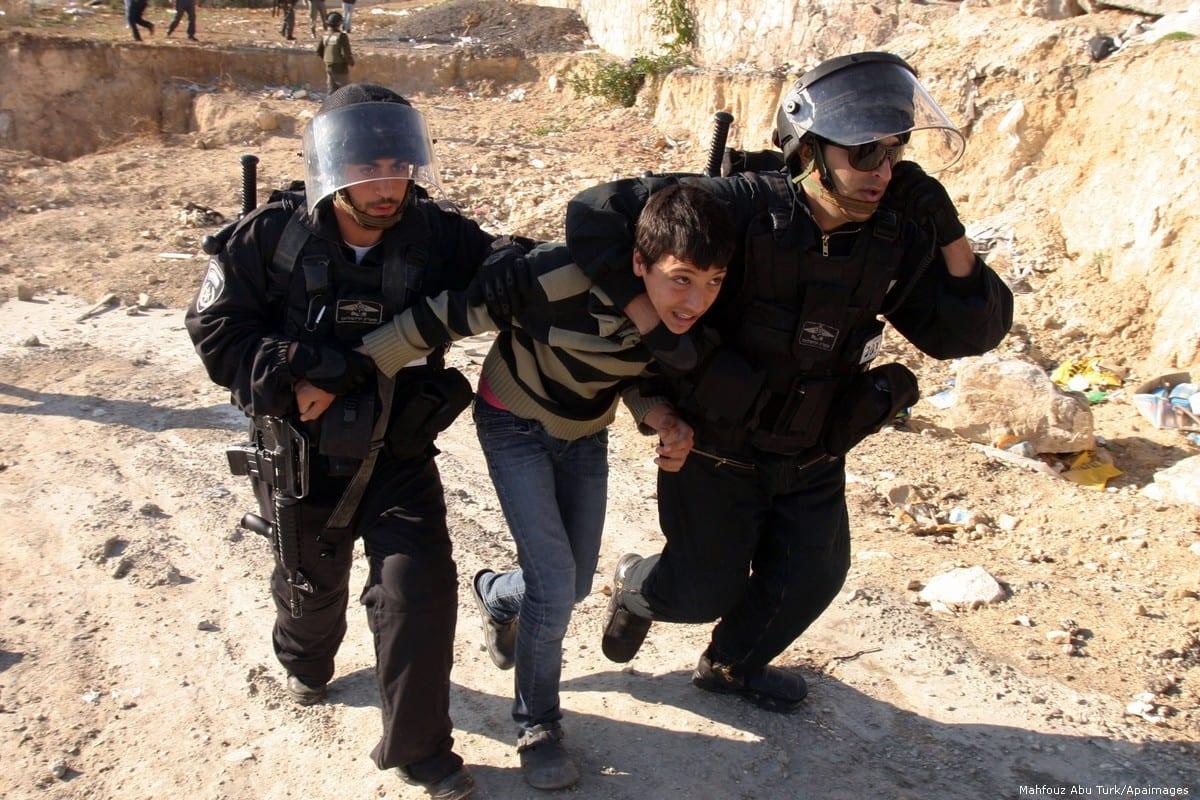 Israeli police officers detain a Palestinian youth on 4 January 2012 [Mahfouz Abu Turk/Apaimages]
