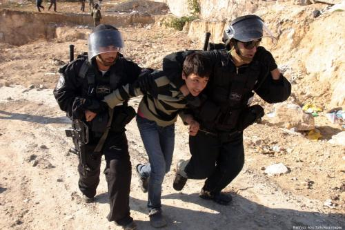 Israeli police officers detain a Palestinian youth on 4 January 2012 [Mahfouz Abu Turk/Apaimages]