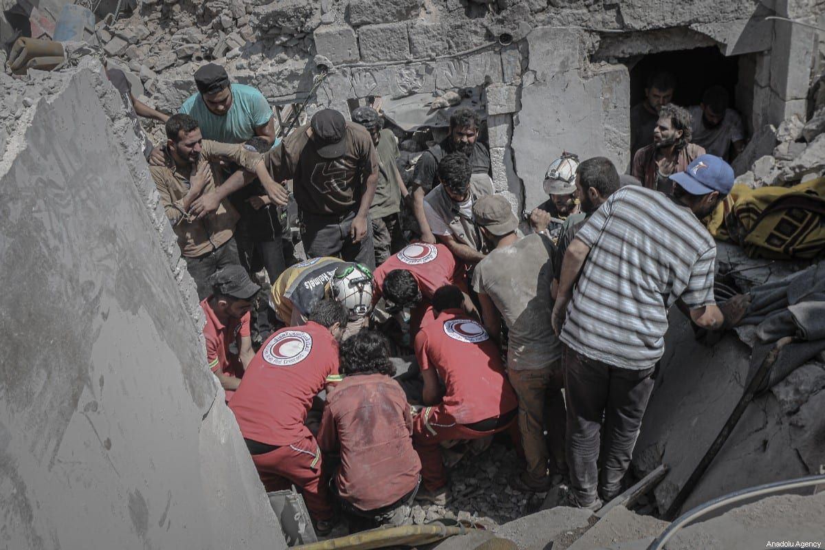 Civil defence crews and locals conduct search and rescue works amid debris after airstrikes of Assad Regime's warplanes hit the de-escalation zone of Ariha in Idlib, Syria on July 12, 2019 [Muhammed Said / Anadolu Agency]