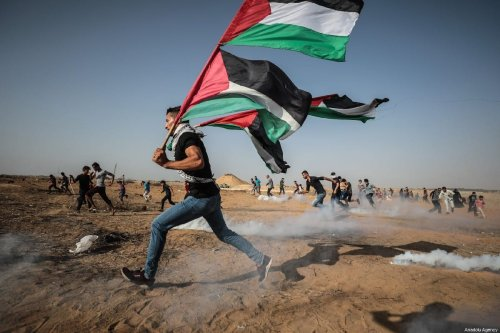 """A protestor runs with the Palestinian flag, as Israeli forces fire tear gas during a demonstration during the """"Great March of Return"""" at Israel-Gaza border in east of Khan Yunis, Gaza on July 12, 2019 [Mustafa Hassona / Anadolu Agency]"""