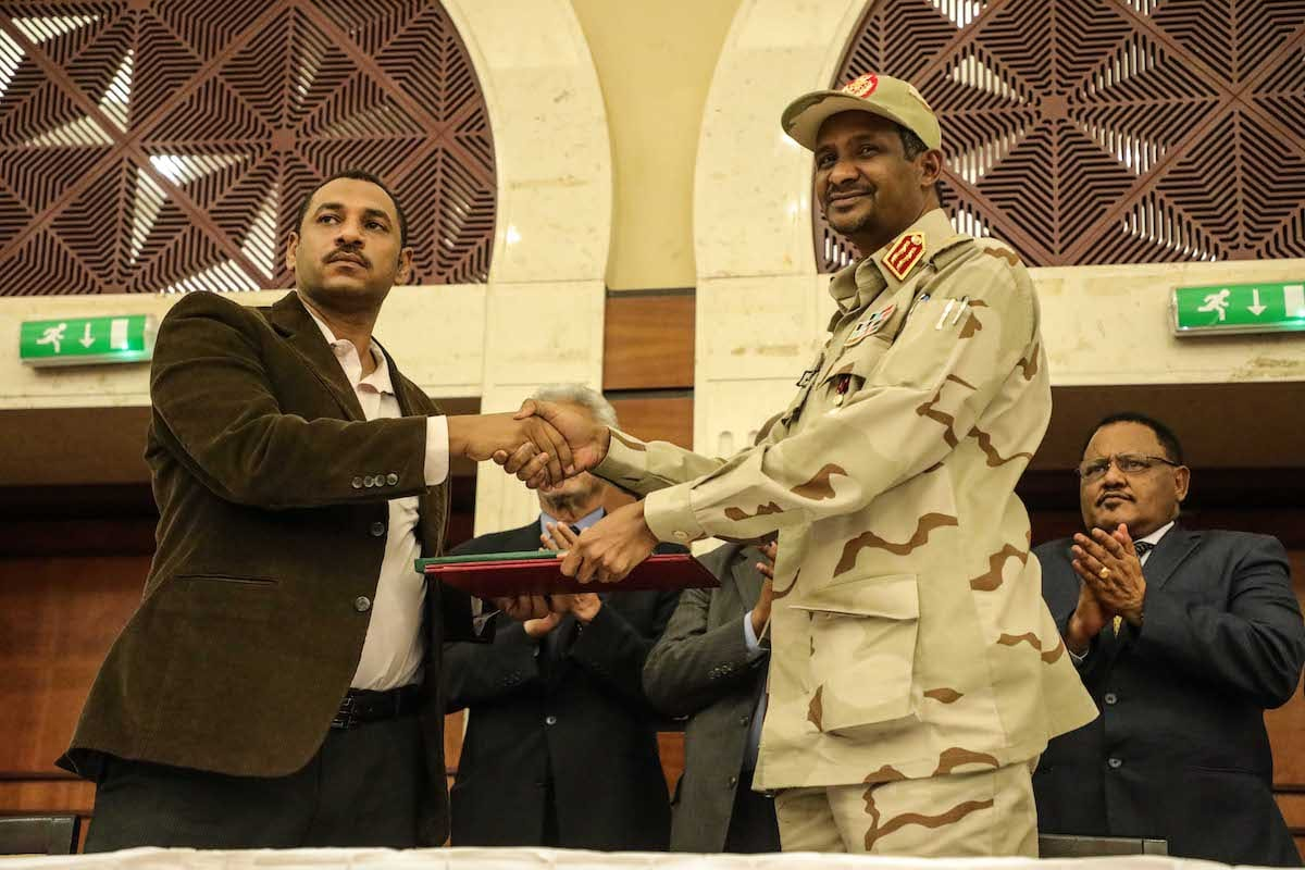 Sudanese General and Vice President of Sudanese Transitional Military Council, Mohamed Hamdan Dagalo (R) and Sudan's Forces of Freedom and Change coalition's leader Ahmad al-Rabiah (L) shake hands after signing an agreement in Khartoum on 17 July 2019. [Mahmoud Hjaj - Anadolu Agency]