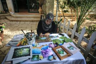 Lin al-Hac, a 21 years old Palestinian woman, colors grape leaves with oil colors, turning them into pieces of art, in Gaza City, Gaza on 16 July 2019. [Ali Jadallah/Anadolu Agency]