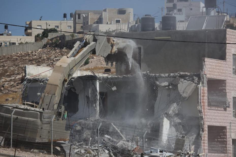 Israeli soldiers demolish a 2 storey building with bulldozers as they have started to demolish buildings belonging to Palestinians on the grounds that the ten buildings are close to wire barriers, which are continuation of the separation wall in Wadi al-Hummus neighborhood of Sur Baher region of East Jerusalem on 22 July 2019. [ Issam Rimawi - Anadolu Agency ] ( Issam Rimawi - Anadolu Agency )