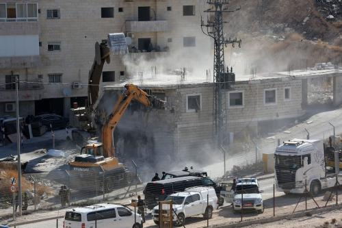 A 2-storey building is being demolished with bulldozers under Israeli soldiers supervision as they have started to demolish buildings belonging to Palestinians on the grounds that the ten buildings are close to wire barriers, which are continuation of the separation wall in Wadi al-Hummus neighborhood of Sur Baher region of East Jerusalem on 22 July 2019. [Wisam Hashlamoun - Anadolu Agency]