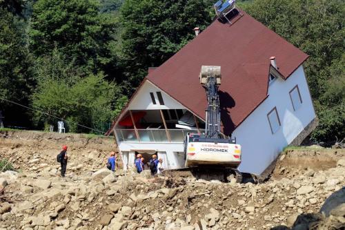 A bulldozer demolishes a house toppled in stream bed due to heavy rains and landslides in Esmahanim village of Akcakoca district, Duzce, Turkey on 22 July 2019. [Tayyib Hoşbaş - Anadolu Agency]