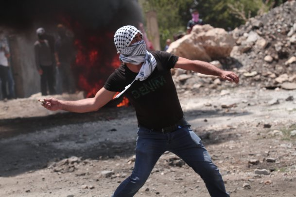 A Palestinian demonstrator throws a rock in response to Israeli forces' intervention during a protest against the construction of Jewish settlements and the separation wall in Qafr Qaddum village in Nablus, West Bank on 26 July 2019 [Nedal Eshtayah/Anadolu Agency]