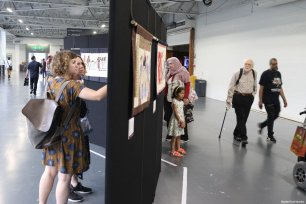 Guests look at the Palestinian tapestries on display at the Palestine Expo 2019 on 6 July 2019 in London, UK [Middle East Monitor]
