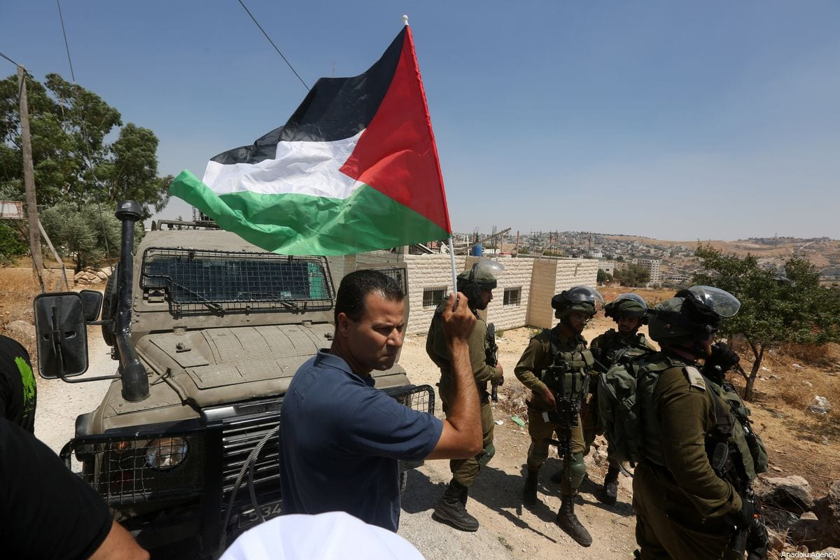 A man carries a Palestinian flag as a reaction to demolition of some of Palestinian houses by Israel in Sur Baher town on the southeastern outskirts of East Jerusalem on August 02, 2019 [Wisam Hashlamoun / Anadolu Agency]