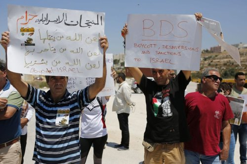 Palestinians hold banners during a demonstration demanding boycott against Israeli products in response to cutting of Palestinian tax revenues in Ramallah, West Bank on 6 August 2019. [Issam Rimawi - Anadolu Agency]