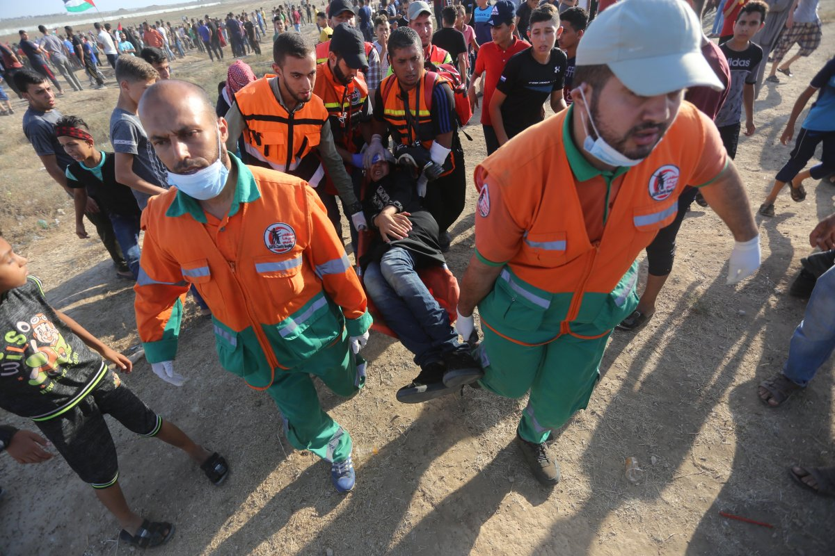 Medics carry an injured Palestinian after Israeli forces shot at protesters during the Great March of Return in Gaza on Friday 17 August 2019 [Mohammed Asad/Middle East Monitor]