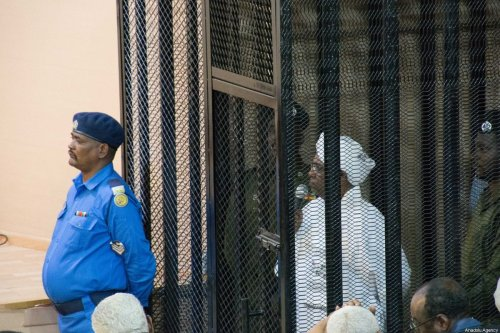 Sudan's ousted President Omar al-Bashir sits in a defendant's cage during his trial of illegal acquisition and use of foreign funds in Khartoum, Sudan on August 31, 2019 [Mahmoud Hjaj / Anadolu Agency]
