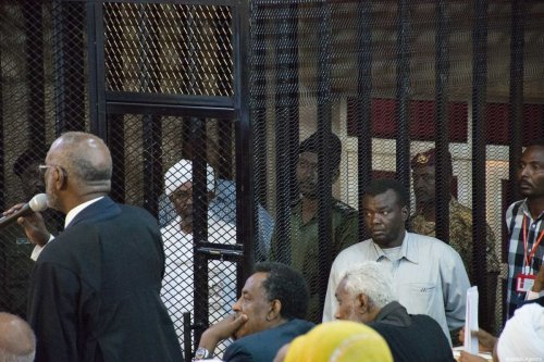 Sudan's ousted President Omar Al-Bashir sits in a defendant's cage during his trial of illegal acquisition and use of foreign funds in Khartoum, Sudan on 31 August 2019 [Mahmoud Hjaj/Anadolu Agency]