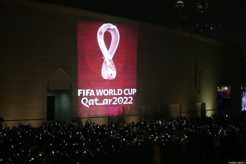 Hundreds of people take a photo as the official logo of the 'FIFA World Cup Qatar 2022' is reflected on a wall in Doha, Qatar on 3 September 2019 [Mohammed Dabbous/Anadolu Agency]