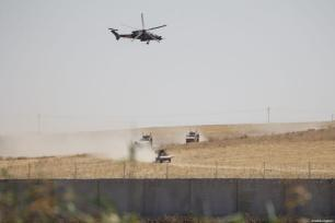 A photo taken from Turkey's Sanliurfa province shows the armoured vehicles and helicopters as Turkey, US start first joint ground patrols as part of efforts to establish safe zone east of Euphrates in Syria on September 08, 2019 [Emin Sansar / Anadolu Agency]