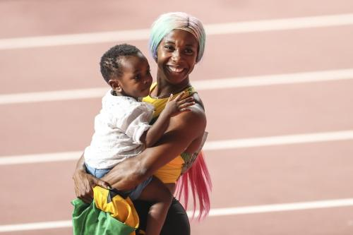 Shelly-Ann Fraser-Pryce of Jamaica celebrates with her son Zyon after winning the women's 100m final during the IAAF World Athletics Championships 2019 at the Khalifa Stadium in Doha, Qatar, 29 September 2019. [Serhat Çağdaş - Anadolu Agency]