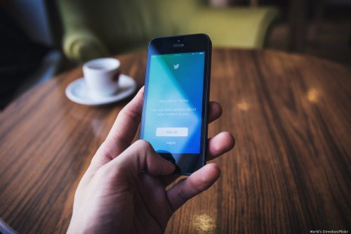 Twitter logo is displayed on the screen of an Apple Iphone
