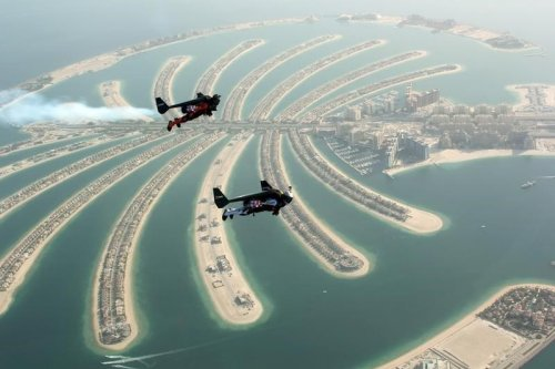 An aerial view taken from a sea plane shows Swiss pilot and original Jetman Yves Rossy (front) and Vince Reffett flying over Dubai's Palm Island, Dubai, United Arab Emirates 12 May 2015. [REUTERS/Lara Sukhtian]