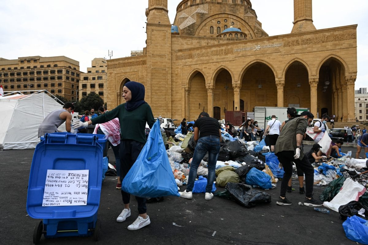 A young woman sorts recycling into a bin in front of the Mohammad al-Amin mosque in Beirut, 23 October 2019. [Thomson Reuters Foundation/Finbar Anderson]