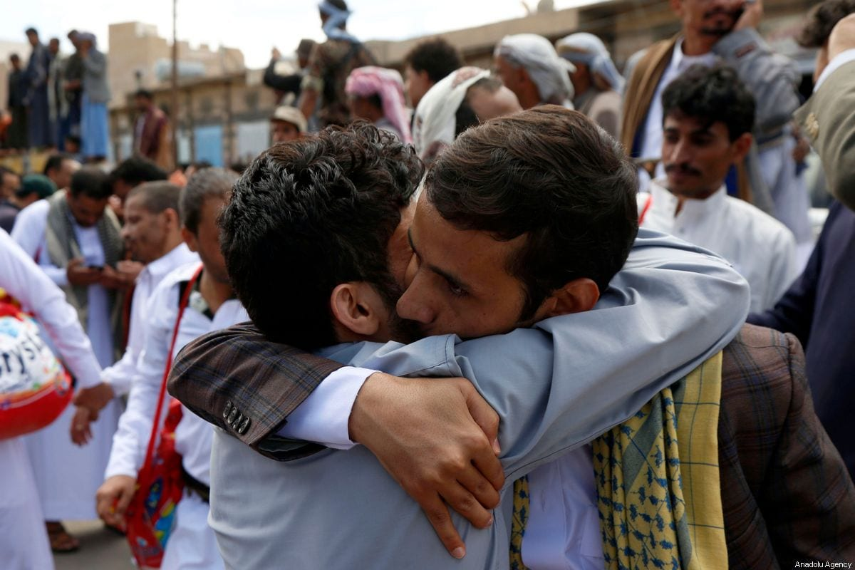 People greet their newly released relatives outside the Central Prison in the Yemeni capital Sanaa, on September 30, 2019. [Mohammed Hamoud - Anadolu Agency]