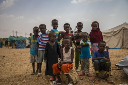 Sudanese children pose for a photo at a tent site in Khartoum, Sudan on 30 September 2019 [Mahmoud Hajaj/Anadolu Agency]