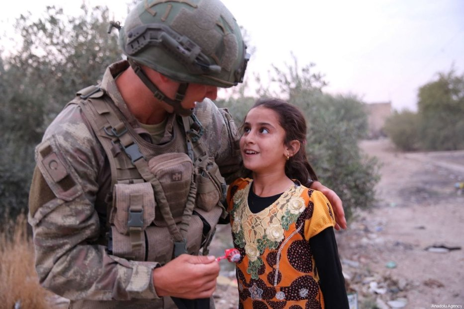 A Turkish soldier gives a candy to a kid after Ras Al Ayn's Tell Halaf village was cleared of militants, as part of Turkey's Operation Peace Spring in Syria on October 19, 2019 [Behçet Alkan / Anadolu Agency]