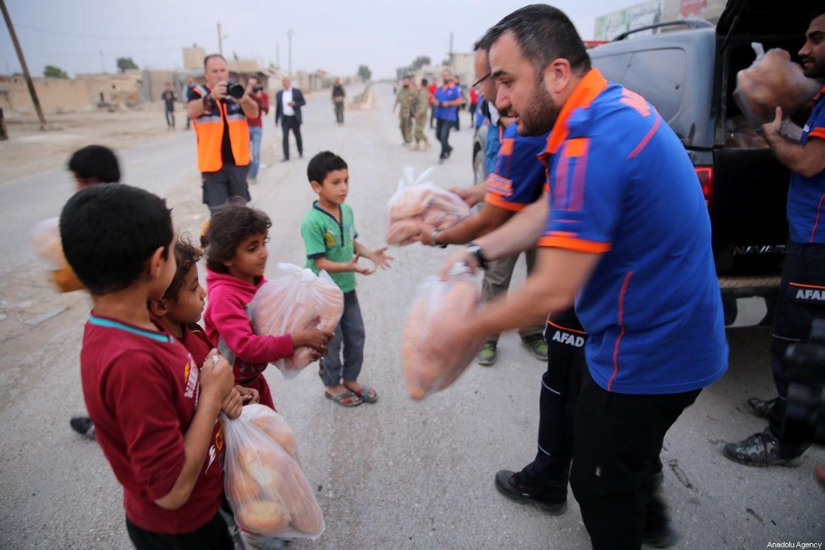 Syrians receive food aid packages in Syria on October 19, 2019 [Behçet Alkan/Anadolu Agency]