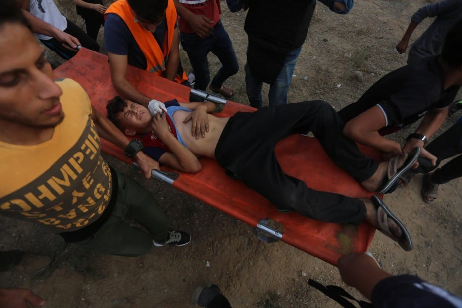 An injured Palestinian is being carried away after Israeli forces attacked protesters during the Great March of Return on 25 October 2019 [Mohammed Asad/Midde East Monitor]